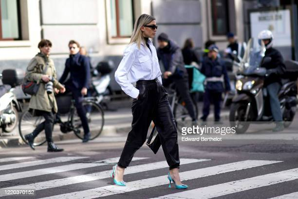 Guest wears sunglasses, a white shirt, black leather pants, blue high heels shoes, outside Sportmax, during Milan Fashion Week Fall/Winter 2020-2021...