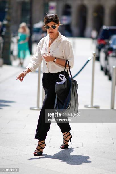 A guest wears sunglasses a white shirt black pants a black bag outside Alexis Mabille during Paris Fashion Week Haute Couture Fall/Winter 20172018 on...