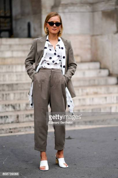 A guest wears sunglasses a white shirt with printed black dots a blazer jacket suit pants white shoes outside Stella Mccartney during Paris Fashion...