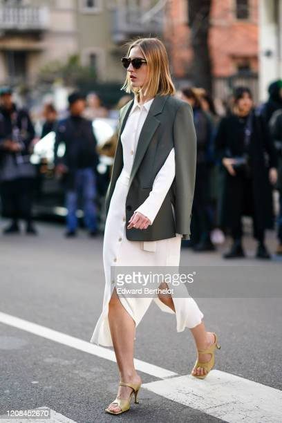 A guest wears sunglasses a white shirtdress a grey jacket mustardyellow sandals outside Bottega Veneta during Milan Fashion Week Fall/Winter 20202021...