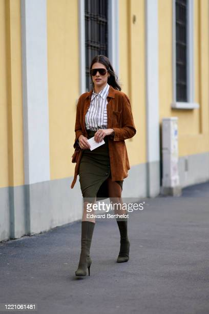Guest wears sunglasses, a white striped shirt, a brown GZ suede jacket, a green/khaki skirt, high heel pointy boots, outside Tod's, during Milan...