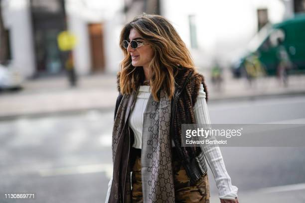 A guest wears sunglasses a white sweater a grey Gucci scarf a sleeveless fur vest camouflage print pants during London Fashion Week February 2019 on...
