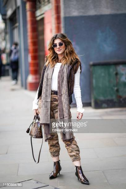 A guest wears sunglasses a white sweater a grey Gucci scarf a sleeveless fur vest camouflage print pants shiny transparent vinyl black boots a Louis...