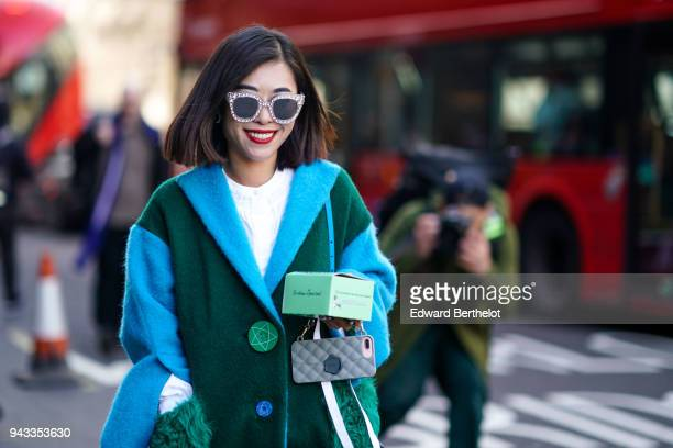 A guest wears sunglasses a white top a green and blue coat with fluffy pockets a bag during London Fashion Week February 2018 on February 16 2018 in...