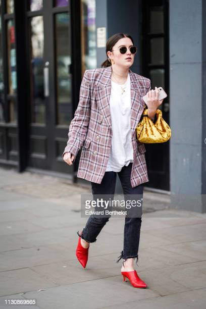 A guest wears sunglasses a white top a grey and pink checkered double breasted jacket black ripped hem jeans red mules a shiny yellow velvet bag...