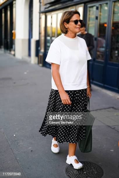 Guest wears sunglasses, a white top, a large forest-green tote bag, a black pleated skirt with white polka dots, white open sneakers, outside 24S...
