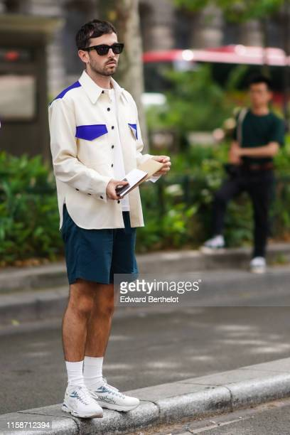 Guest wears sunglasses, a white top, a white jacket with blue pocket-flaps and inserts, deep petrol-blue shorts, white socks, white Asics sneakers,...