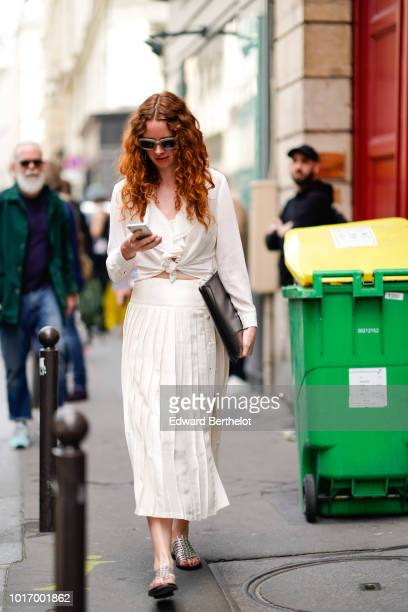 A guest wears sunglasses a white top a white pleated skirt silver sandals holds a mobile phone outside Thom Browne during Paris Fashion Week Menswear...