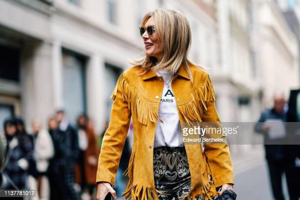 A guest wears sunglasses a white top a yellow fringed jacket golden and silver paisley design damask tapestry pants during London Fashion Week...