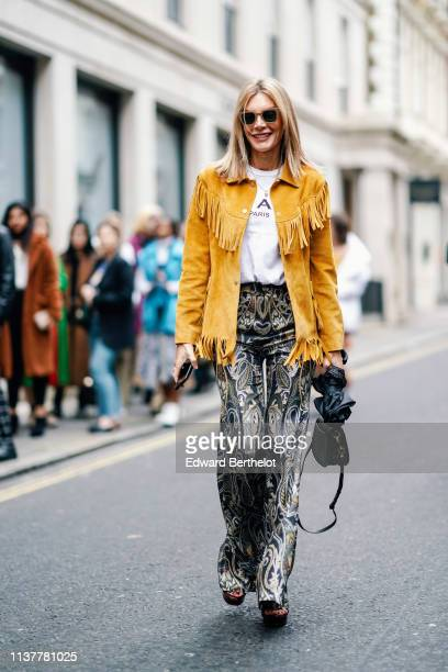A guest wears sunglasses a white top a yellow fringed jacket golden and silver paisley design damask tapestry pants a green bag black platform...