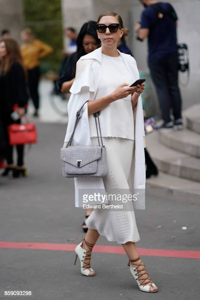 A guest wears sunglasses a white top white jacket a gray bag shoes outside Andrew GN during Paris Fashion Week Womenswear Spring/Summer 2018 on...