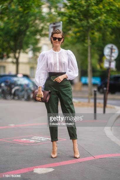 Guest wears sunglasses, a white top with a lace insert, forest-green high-waist cuffed crop pants, a brown Dior bag, shiny nude color pointy pumps,...