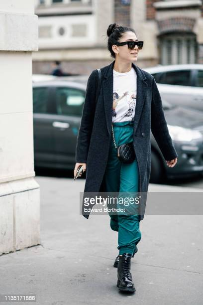 A guest wears sunglasses a white top with printed images of Oprah Winfrey and Anna Wintour green pants a grey coat a black Chanel round bag shiny...