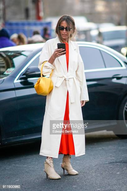 A guest wears sunglasses a white trench coat an orange dress a yellow bag holds a smartphone outside Proenza Schouler during Paris Fashion Week Haute...