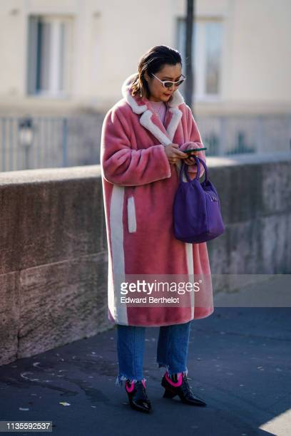 Guest wears sunglasses, a white trimmed pink fluffy faux fur coat, a purple bag, ripped hems jeans, black and neon pink pointy boots, outside Dries...