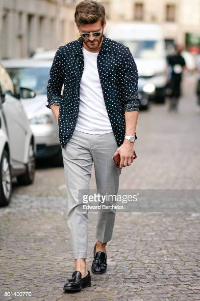 A guest wears sunglasses a white tshirt a black jacket with white dots printed gray pants black leather shoes outside the Kenzo show during Paris...