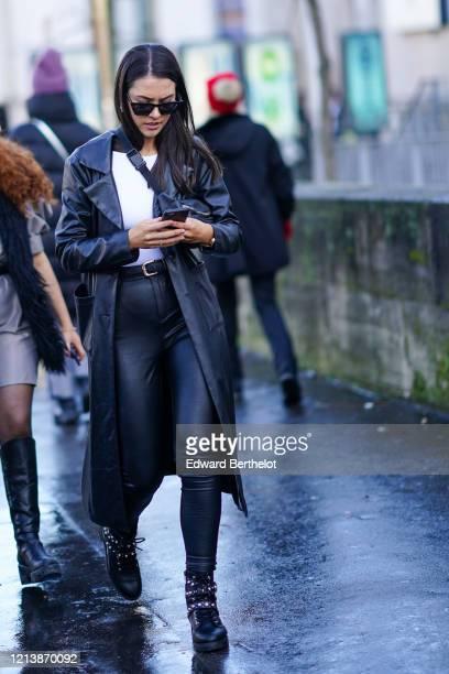 Guest wears sunglasses, a white t-shirt, a black leather long coat, a belt, black leather pants, studded shoes, outside Rokh, during Paris Fashion...