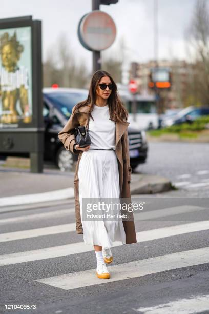 Guest wears sunglasses, a white t-shirt, a brown trench coat, a white pleated skirt, sneakers and socks, a black leather bag, outside Lacoste, during...