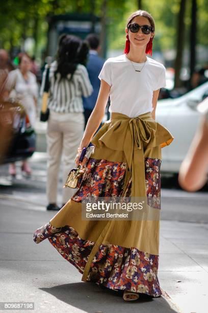 A guest wears sunglasses a white tshirt a flower print skirt outside the Zuhair Murad during Paris Fashion Week Haute Couture Fall/Winter 20172018 on...