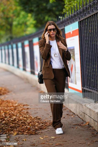 A guest wears sunglasses a white tshirt a necklace depicting the letter C a brown blazer jacket flared pants white sneakers a bag outside Lacoste...