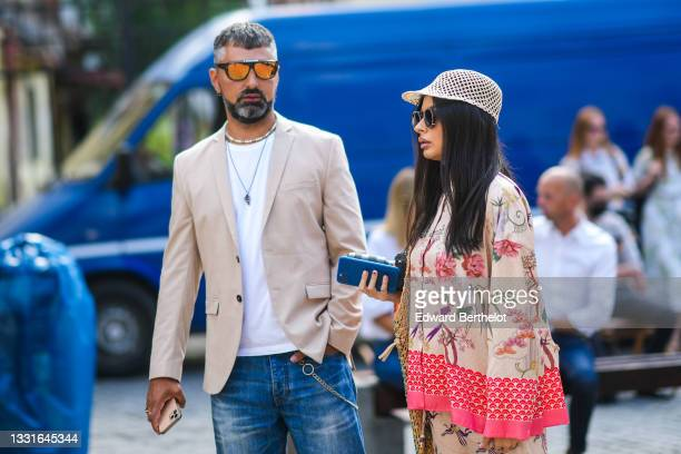 Guest wears sunglasses, a white t-shirt, a white and black pearls necklace, a silver chain pendant necklace, a beige blazer jacket, blue faded denim...