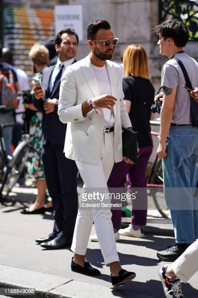 A guest wears sunglasses a white tshirt a white jacket a black Hermes belt white cuffed pants black slippers a black clutch outside Thom Browne...