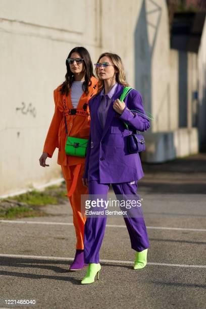 Guest wears sunglasses, a white t-shirt, an orange jacket, a neon green bag, flare pants, purple shoes, outside Alberta Ferretti, during Milan...