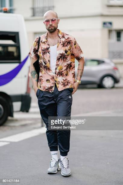 A guest wears sunglasses a white tshirt and opened flower print shirt black pants gray shoes outside the Kenzo show during Paris Fashion Week...