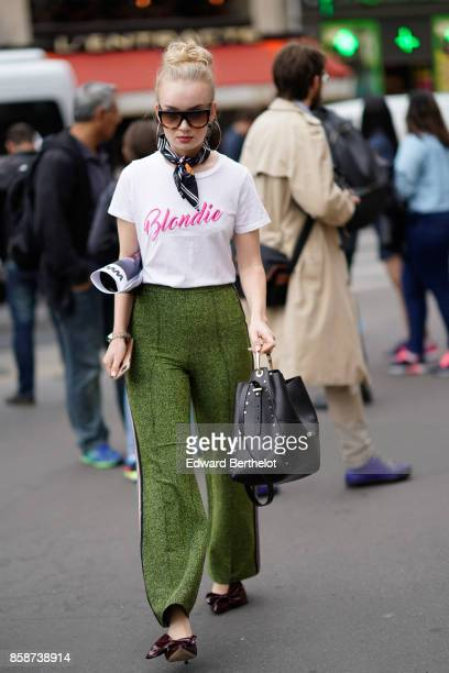 A guest wears sunglasses a white tshirt blondie print green pants outside Stella Mccartney during Paris Fashion Week Womenswear Spring/Summer 2018 on...