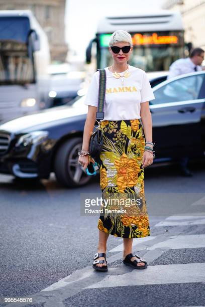 """Guest wears sunglasses, a white t-shirt with the incription """"MAMMA"""", a yellow skirt with embroidered flowers, black shoes , outside Schiaparelli,..."""