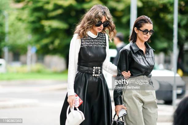 A guest wears sunglasses a white turtleneck a black leather sleeveless dress with a black lace illusion neckline a black belt with a bejeweled buckle...
