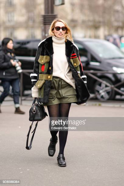 A guest wears sunglasses a white turtleneck a coat a khaki green skirt tights black shoes outside Miu Miu during Paris Fashion Week Womenswear...