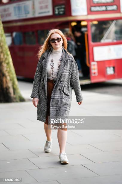 A guest wears sunglasses a white turtleneck a grey Prince of Wales check coat an orange pleated skirt beige sneakers during London Fashion Week...