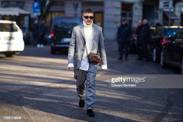 Guest wears sunglasses, a white turtleneck pullover, a gray blazer jacket a Vuitton brown monogram bag with an orange chain, gray pants, black shoes,...