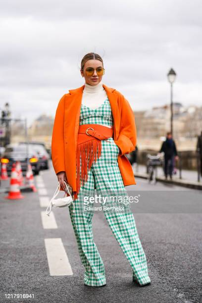 Guest wears sunglasses, a white turtleneck pullover, an orange jacket, an orange large belt with fringes, a green and white checked jumpsuit, a white...