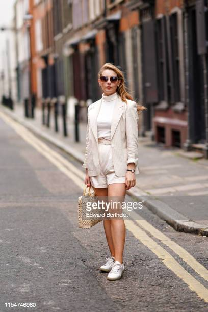 A guest wears sunglasses a white turtleneck top a blazer jacket a straw bag white shorts white sneakers during London Fashion Week Men's June 2019 on...