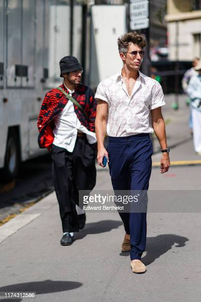 A guest wears sunglasses a white Valentino shirt navy blue pants camel suede slippers outside Acne Studios during Paris Fashion Week Menswear...