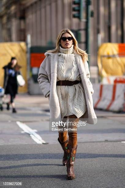 Guest wears sunglasses, a white wool knitted pullover, a belt, a fluffy coat, brown suede pants, brown leather floral print cowboy boots, outside...