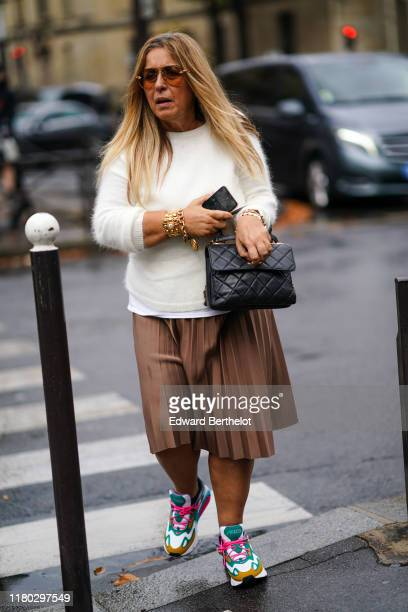 A guest wears sunglasses a white wool pullover a black quilted bag a brown pleated skirt colored sneakers a golden bracelet outside Miu Miu during...
