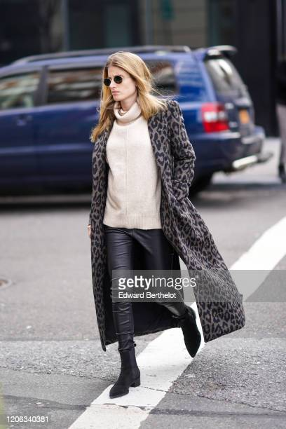 A guest wears sunglasses a white wool pullover a gray leopard print long coat black leather pants pointy boots during New York Fashion Week Fall...
