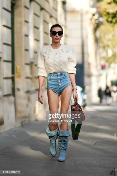 Guest wears sunglasses, a white wool pullover, blue denim mini shorts, a Fendi bag, blue denim boots, outside Alessandra Rich, during Paris Fashion...