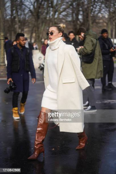 Guest wears sunglasses, a white wool turtleneck pullover, an oversized coat, black leather pointy high heel boots, outside Chanel, during Paris...