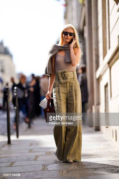 A guest wears sunglasses a wool pullover a tank top flared pants outside Altuzarra during Paris Fashion Week Womenswear Spring/Summer 2019 on...