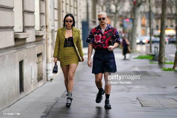 Guest wears sunglasses, a yellow and black houndstooth pattern printed jacket, long earrings, a necklace, a black lace mesh embroidered, a short...