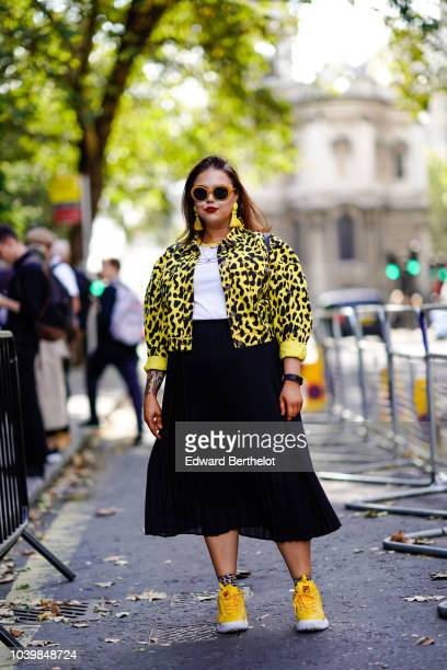 A guest wears sunglasses a yellow and black printed jacket a white top a black skirt yellow sneaker shoes during London Fashion Week September 2018...