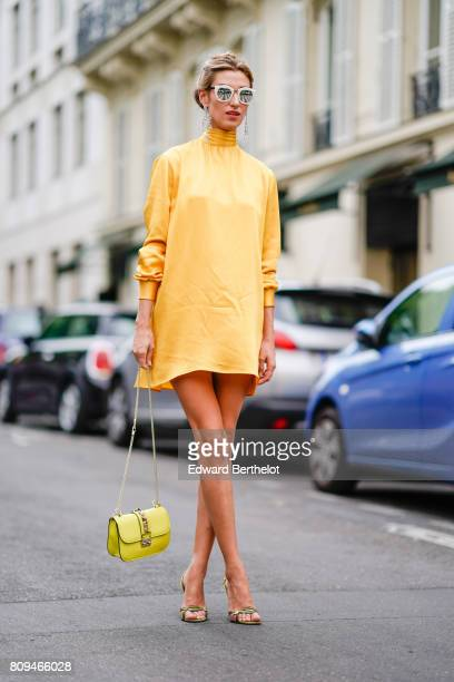 A guest wears sunglasses a yellow dress a yellow Valentino Rockstud bag yellow heels shoes outside the Valentino show during Paris Fashion Week Haute...