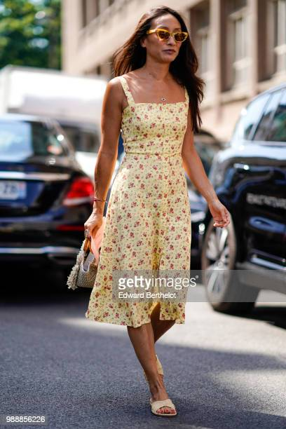 A guest wears sunglasses a yellow floral print dress outside Acne Studios during Paris Fashion Week Womenswear Fall Winter 2019 on July 1 2018 in...