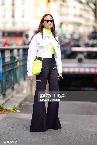 A guest wears sunglasses a yellow neon colored turtleneck top a neon yellow bag black flared pants a white jacket outside Balmain during Paris...