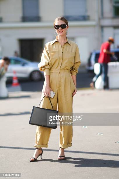 A guest wears sunglasses a yellow outfit a black rectangular bag outside Acne during Paris Fashion Week Haute Couture Fall/Winter 2019/2020 on June...