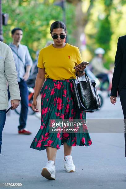Guest wears sunglasses, a yellow top with a red heart and a red A logo, a black alligator pattern shopping bag, a forest green pleated skirt with hot...